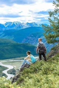 배낭을 메고 산 정상에 있는 두 명의 관광객과 한 여성이 전망을 즐깁니다. 여행 컨셉