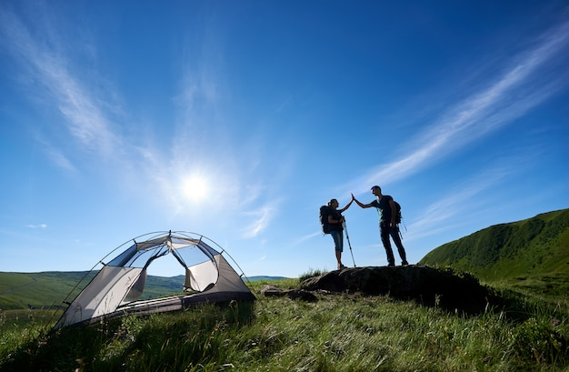Two tourists with trekking sticks in backpacks give each other a high five near the camping in the mountains under the blue sky with a bright sun.