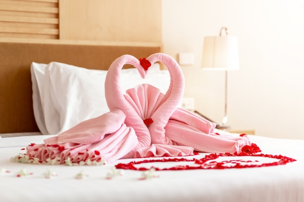 Two towel swans shaped on the bed