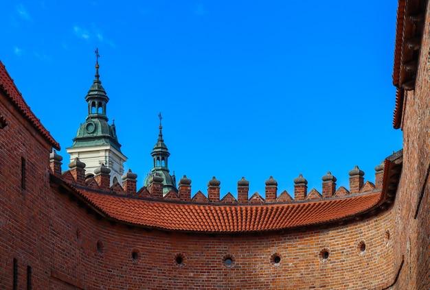 ワルシャワのバービカンポーランドの尖塔と赤レンガの壁のある2つの塔