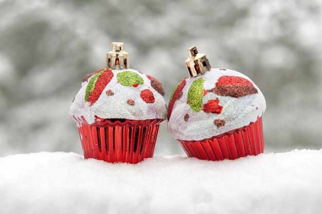 雪の冬の休日の背景に2つのおもちゃのケーキ