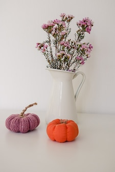 Two toy knitted purple and orange miniature pumpkin and a white jar with flowers on white
