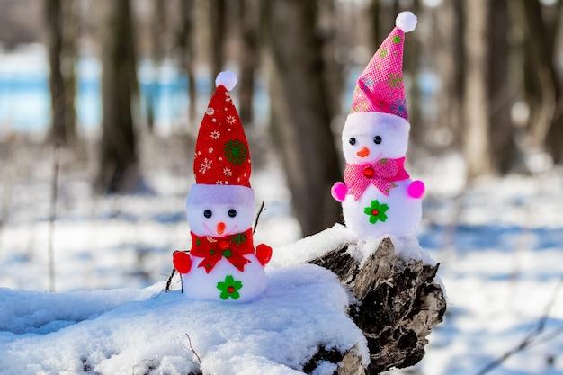 晴れた日の森の中の 2 つのおもちゃの雪だるま