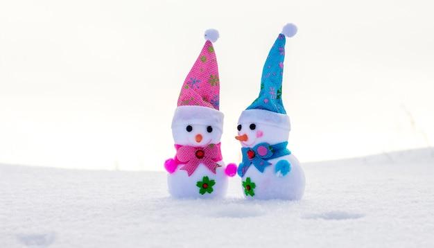 눈 속에서 두 개의 장난감 눈사람입니다. 우호적인 관계와 즐거운 소통의 개념_