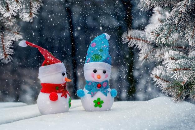 Два игрушечных снеговика в зимнем лесу возле заснеженных елок во время снегопада. рождественская и новогодняя открытка