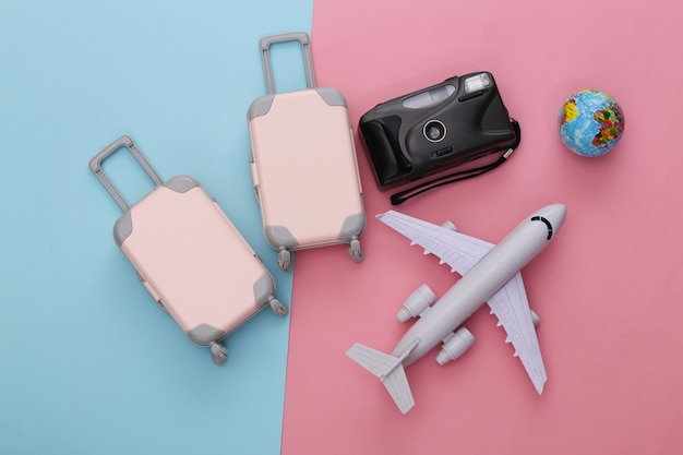 Two toy travel luggage, air plane and globe on pink blue pastel. travel planning
