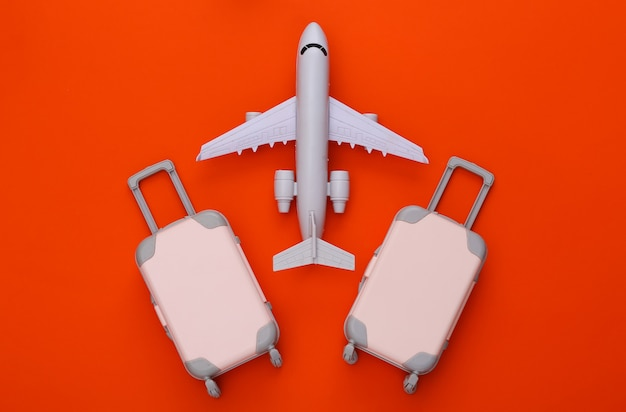 Two toy travel luggage and air plane on orange. travel planning
