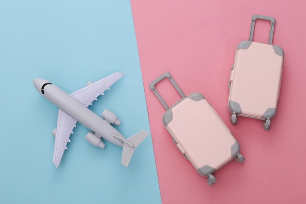 Two toy travel luggage and air plane on pink blue pastel. travel planning