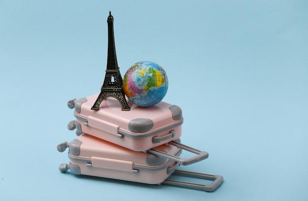 두 장난감 여행 가방, 에펠 탑 입상 및 파랑에 글로브. 여행 계획.