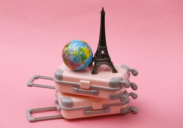 두 장난감 여행 가방, 에펠 탑 입상 및 핑크 글로브. 여행 계획.