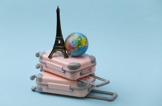 Two toy travel luggage, eiffel tower figurine and globe on blue. travel planning.