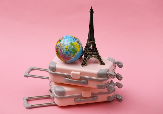 Two toy travel luggage, eiffel tower figurine and globe on pink. travel planning.