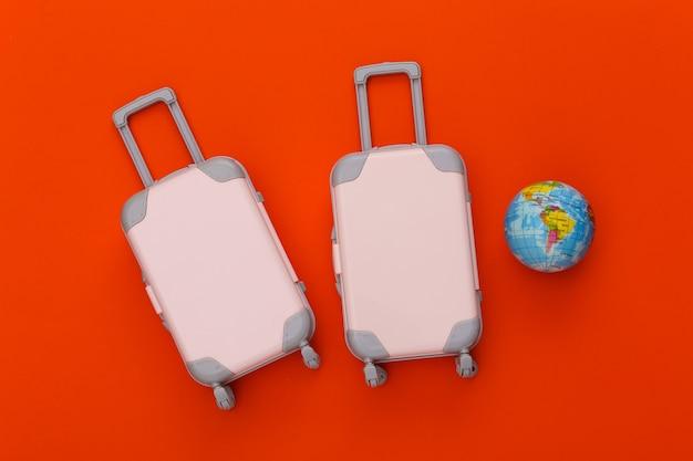 Two toy travel luggage, globe on orange. travel planning