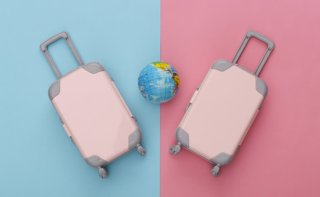 Two toy travel luggage and globe on pink blue pastel. travel planning