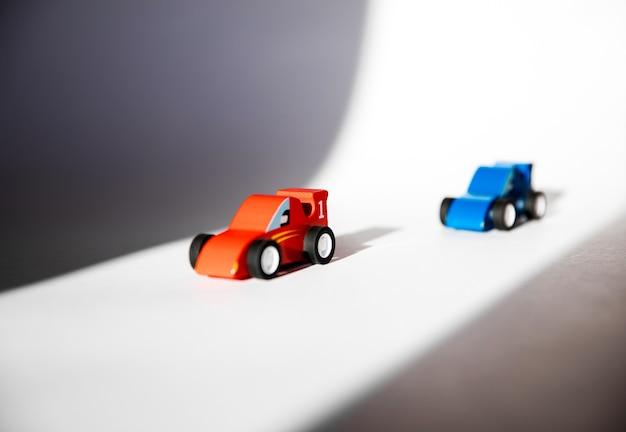 빨간색과 파란색 장난감 두 대의 나무 경주용 자동차가 빛과 그림자의 임시 트랙에서 경쟁했습니다.