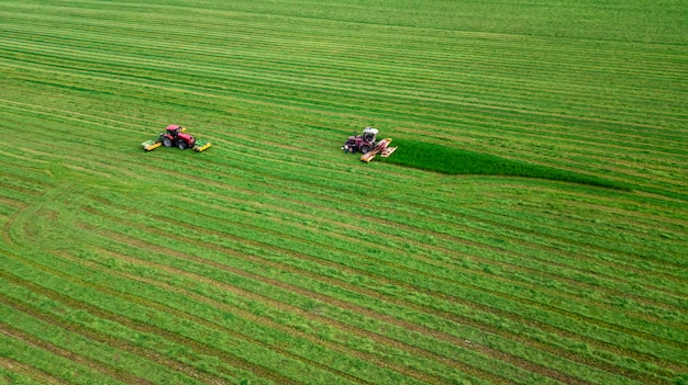 Two tractors mows the grass on a green field aerial view