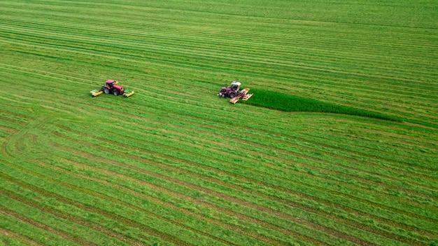 Два трактора косит траву на зеленом поле с высоты птичьего полета
