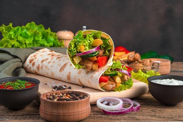 Два традиционных восточных блюда шаурмы с мясом и овощами на коричневой стене с ингредиентами. фастфуд, быстрые перекусы.