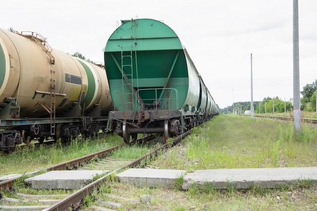 客車とタンク車が交差する鉄道の交差点に馬車付きの2両の列車が立っています。