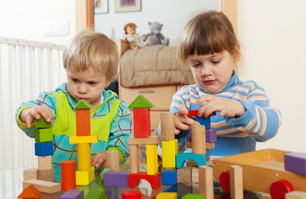 Two  tranquil children playing with wooden toys