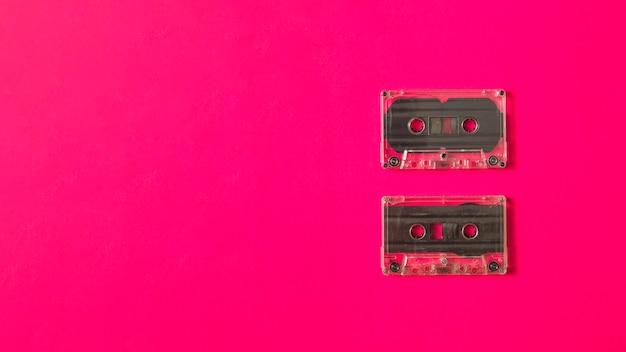 분홍색 배경에 두 개의 투명 카세트 테이프