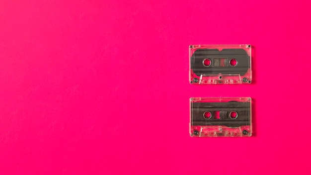 Two transparent cassette tape on pink background