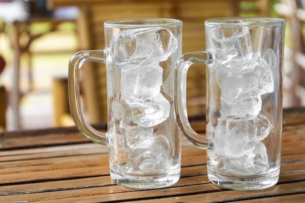 夏のカフェで氷で2つの透明なグラス。水なしの氷入りグラス