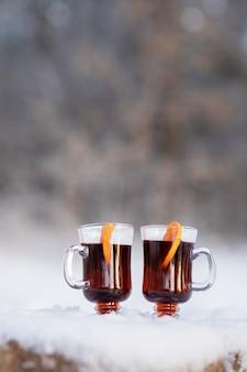 Два прозрачных бокала с вином и дольками апельсина в лесу на заснеженном дереве