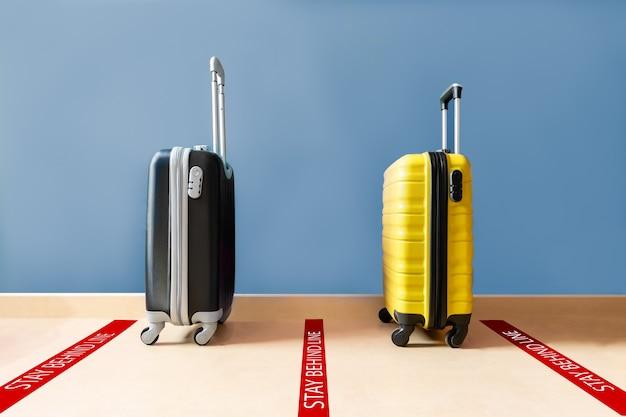 두 개의 여행 가방 하나는 검은 색이고 하나는 노란색이 계속 대기 중입니다. 바닥에 빨간색 표시가 있습니다.