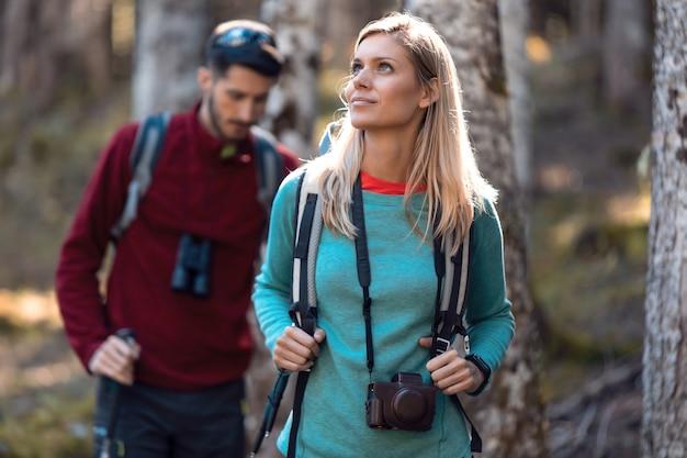 森の風景を見ながらバックパックを持って歩く2人の旅行ハイカー。