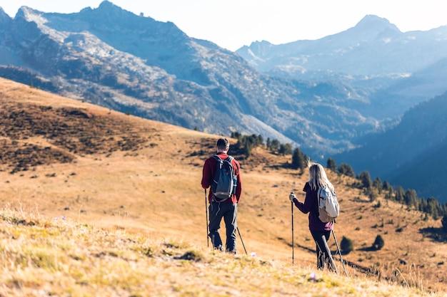 山の風景を見ながらバックパックを持って歩く2人の旅行ハイカー。背面図。