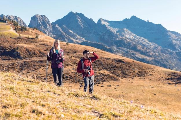 山の風景を見ながらバックパックを持って歩く2人の旅行ハイカー。