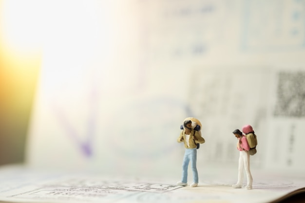 Two of traveler miniature mini figures with backpack standing and talking on passport with immigration stamps