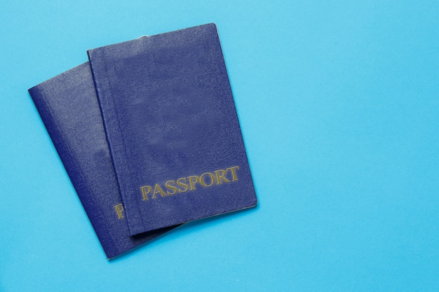 Two travelers passports on blue background. travel concept