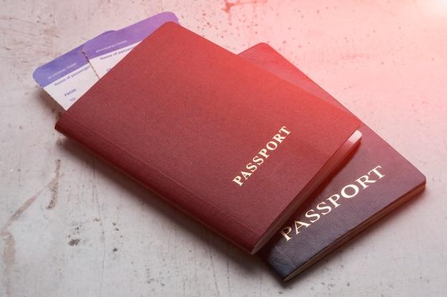 비행기 탑승권과 함께 빨간색과 파란색 두 여행자 여권.