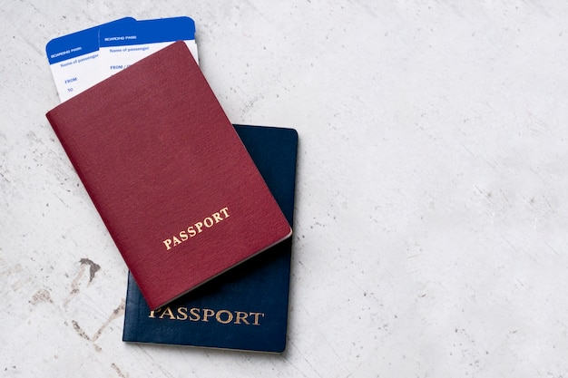 Two travelers passports red and blue with boarding passes for the plane.