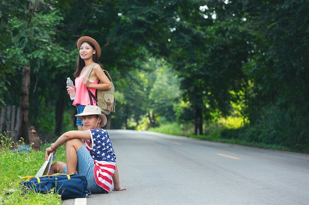 Two travelers sitting on country side street