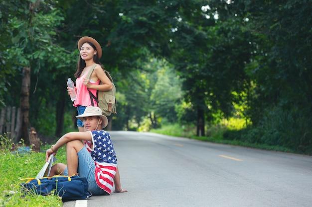 田舎道に座っている2人の旅行者
