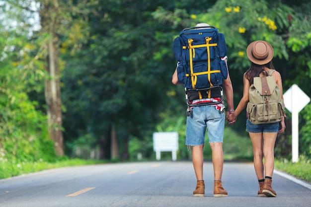 田舎道を歩く2人の旅行者