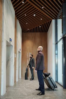 Двое путешествующих бизнесменов с чемоданами ждут лифта в длинном коридоре отеля, идя в свои комнаты
