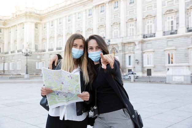 彼らが見ている方向を指している2人の旅行中の友人。彼らは医療用マスクを着用しています。旅行とニューノーマルのコンセプト。