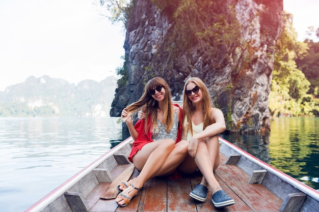Two traveling women, best friends exploring wild nature of khao sok national park. sitting in wood long tail boat on tropical limestone cliffs. lifestyle image. island lagoon.