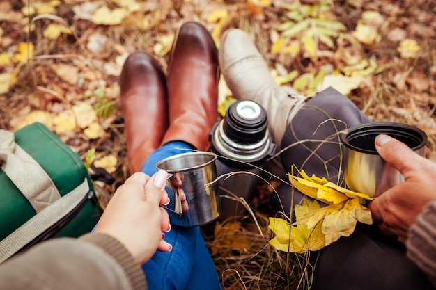 Two travellers having tea in autumn forest
