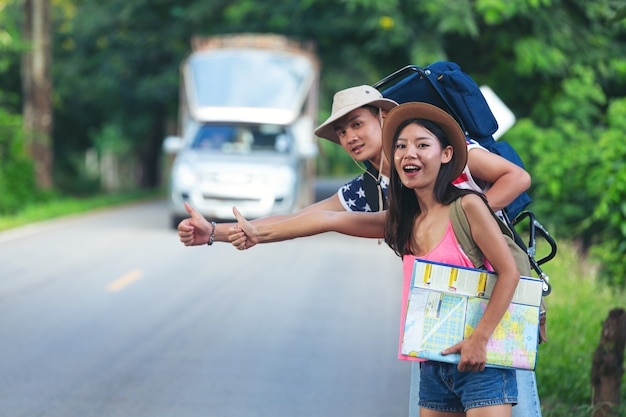 田舎道でヒッチハイクする2人の旅行者