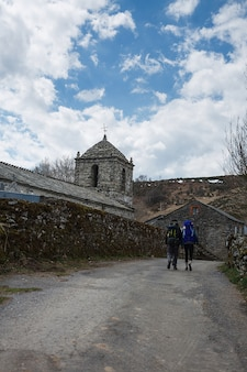 Two travellers walking by the ancient chapel on the way to santiago de compostela