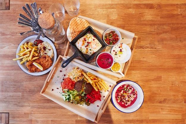 Два подноса с разной едой на деревянном фоне салаты супы картофель фри фрикадельки жареные ...