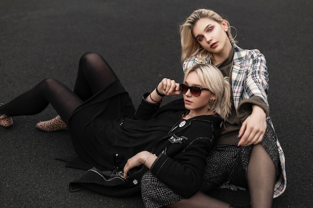 Two trendy modern sisters in fashionable clothes resting on basketball court in city