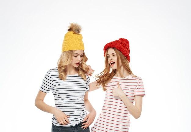 ストライプのtシャツ、色とりどりの帽子、モダンなスタイルの2人のトレンディな女性。高品質の写真