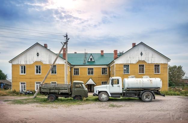 Два грузовика стоят перед желтым жилым домом на соловецких островах