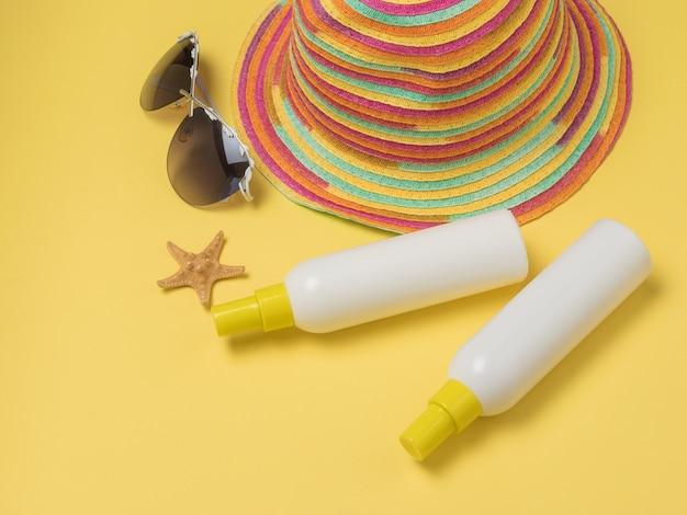 자외선 차단제 튜브 두 개, 모자, 안경. 일광욕을한다. 태양 요법.